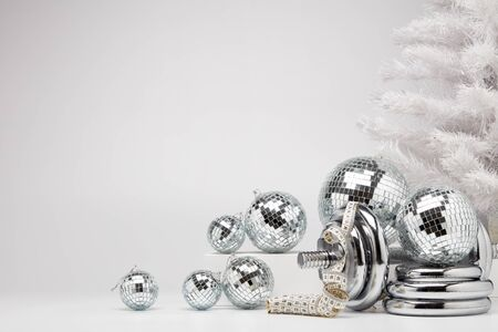 Dumbbells, Christmas fir tree and mirorr balls on white background with copy space. For design of advertising, web design. Christmas and New Year. Fitness, sport or healthy lifestyle concept.