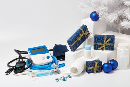 Stethoscope, medical devices, white fir tree, gift boxes and Christmas decorations on white background with copy space. Medical concept. Greeting card. New Year and Christmas.