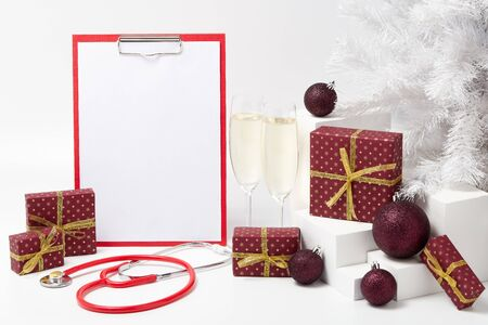 Stethoscope, blank clipboard, two glasses with champagne, fir tree, gift boxes and Christmas decorations on white background with copy space. Medical concept. Greeting card. New Year and Christmas. Stock Photo