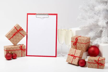Gift boxes, blank clipboard,  two champagne flutes, fir tree and Christmas decoration  on white  background with copy space. Christmas and New Year. For advertising. Greeting card. Winter sale