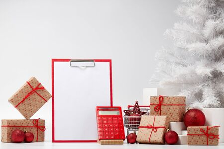 Shopping trolley, gift boxes, clipboard with blank sheet and fir tree with ornaments on white background. Christmas and New Year shopping. Planning budget. Cost of holiday. Winter sale