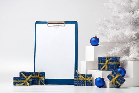 Gift boxes, blank clipboard, fir tree and Christmas decoration  on white  background with copy space. Christmas and New Year. For advertising. Greeting card. Winter sale