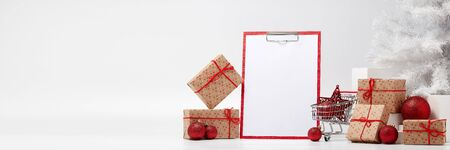 Shopping trolley, gift boxes, blank sheet on clipboard and Christmas decorations isolated on white  background. Christmas and New Year shopping. Winter sale. For design of advertising, web design Stock Photo