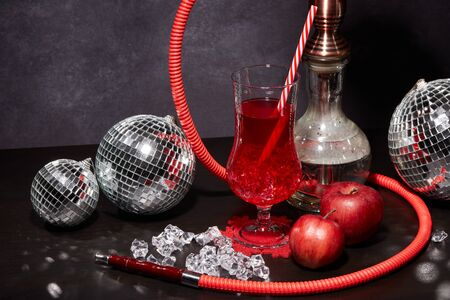 Hookah (shisha), mirror balls (disco ball), glass with cocktail, red apples and ice on dark grey background. New Year and Christmas. Weekend or holiday party