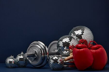 Dumbbell, boxing gloves, skipping rope, mirorr balls on dark blue background with copy space. For design of advertising, web design. Christmas and New Year. Fitness, sport or healthy lifestyle concept Stock Photo