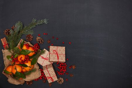 Festive still life: berries, mandarins with leaves on wooden tray with rough napkin from burlap, gift boxes, spices and fir branches on dark background. Top view with copy space. Christmas. New Year
