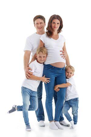 Familia amistosa. Marido con dos hijos están sonriendo y abrazando a la mujer embarazada, aislado en un fondo blanco. Padres felices. Madre embarazada y padre con hijos. Concepto de personas y familia Foto de archivo