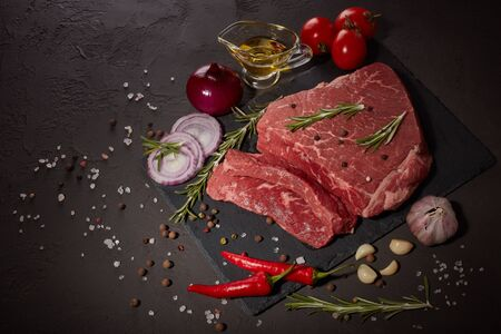 Raw meat beef fillet on stone cutting board, rosemary, set of different peppers, vegatables, olive oil on dark background. Fresh beef piece for steak or grilled barbecue. Top view with copy space 版權商用圖片