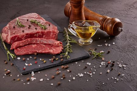 Still life with raw meat beef fillet on black stone cutting board,  rosemary twigs, set of different peppers, salt and olive oil on dark background. Fresh beef piece for steak or grilled barbecue