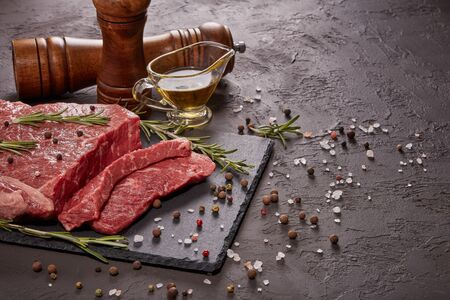 Raw meat beef fillet on black stone cutting board,  rosemary, set of different peppers, salt and olive oil on dark background. Fresh beef piece for steak or grilled barbecue. Top view with copy space 版權商用圖片