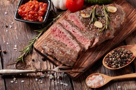 Grilled meat. Medium rare beef steak on wooden cutting board, rosemary twigs, spices and vegatables on brown wooden background. Top view. Steak menu