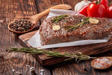 Roasted meat. Grilled beef steak on wooden cutting board, rosemary twigs, spices and vegatables on brown wooden background. Steak menu
