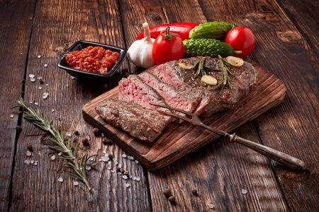 Grilled meat. Medium rare beef steak on wooden cutting board, rosemary twigs, spices and vegatables on brown wooden background. Steak menu