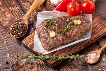 Roasted meat. Grilled beef steak on wooden cutting board, rosemary twigs, spices and vegatables on brown wooden background. Top view. Steak menu