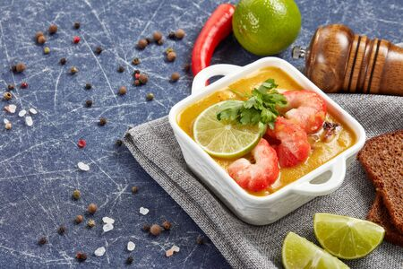 Delicious  fish cream soup with shrimps in white bowl served with spices, lime and pieces of bread on dark blue marble background. Healthy food. Seafood menu