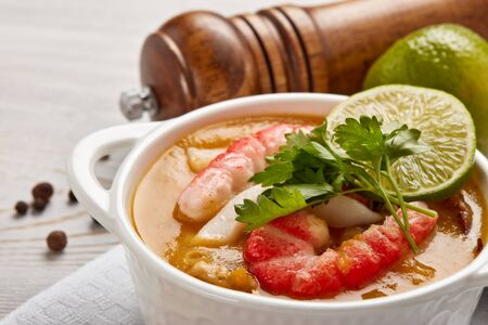 Delicious fish cream soup with shrimps in white bowl served with spices and lime on light wooden background. Healthy food. Seafood menu