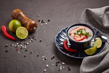 Delicious  fish soup with shrimps in dark blue bowl served with spices and lime on dark grey background. Top view. Healthy food. Seafood menu