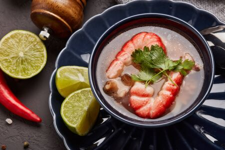 Delicious  fish soup with shrimps in dark blue bowl served with spices and lime on dark grey background. Top view.  Healthy food. Seafood menu Фото со стока