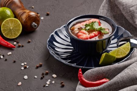 Delicious  fish soup with shrimps in dark blue bowl served with spices and lime on dark grey background.  Healthy food. Seafood menu