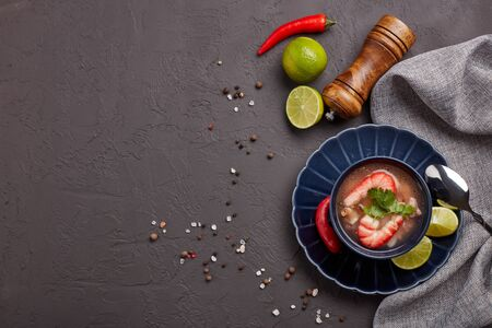 Delicious  fish soup with shrimps in dark blue bowl served with spices and lime on dark grey background. Top view with copy space. Healthy food. Seafood menu