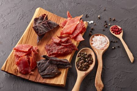 Jerky. Set of various kind of dried spiced meat on wooden tray, diverse peppercorns and salt on wooden spoons  on dark gray background. Top view. Snack for beer.