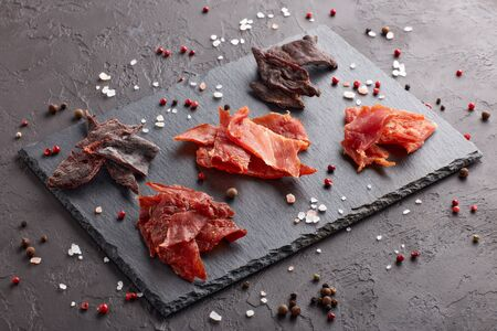 Jerky. Set of various kind of dried spiced meat on black stone cutting board on dark gray background.  Snack for beer.