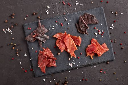 Jerky. Set of various kind of dried spiced meat on black stone cutting board on dark gray background. Top view.  Snack for beer.