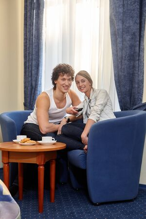 Happy young couple with breakfast are sitting in armchairs and watching TV in living room at home.