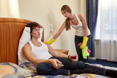 Family problems. Young wife cleaning a room quarrels with the husband lying on  bed. Family conflict.
