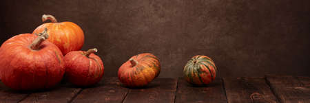 Festive autumn still life with pumpkins on dark wooden surface on brown background with copy space. Concept of autumn harvest, happy Thanksgiving  day or Halloween.