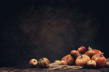 Festive autumn still life with pumpkins, apples and rye ears on dark wooden surface on brown background with copy space. Concept of autumn harvest, happy Thanksgiving  day or Halloween. Stock Photo