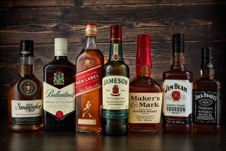 St.Petersburg, Russia - April  2020 - Bottles of several most popular whiskey (whisky) brands on dark wooden background.