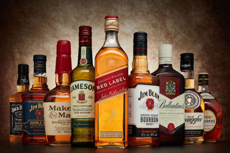 St.Petersburg, Russia - April  2020 - Bottle of Johnnie Walker Red Label blended scotch whisky on background of other popular brands of whiskey (whisky) on dark  background 新闻类图片