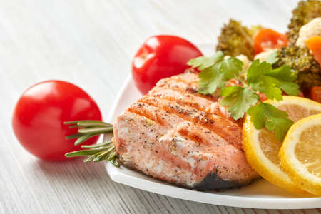 Grilled salmon fillet  garnished with vegetables, lemon, tomato, herbs lying on plate on wooden background. Healthy food. Keto diet.