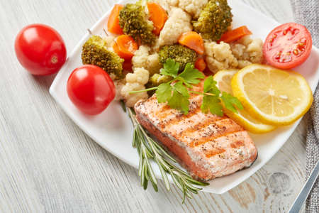 Grilled salmon fillet  garnished with vegetables, lemon, tomato, herbs lying on plate on wooden background. Top view. Healthy food. Keto diet.