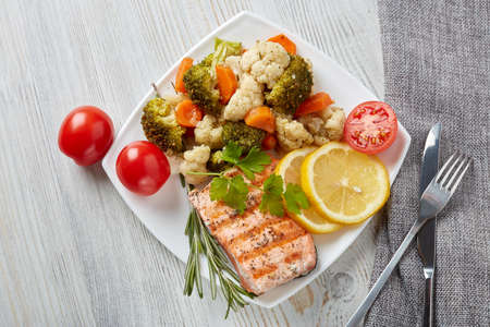 Grilled salmon fillet  garnished with vegetables, lemon, tomato, herbs lying on plate on wooden background. Top view.Healthy food. Keto diet.