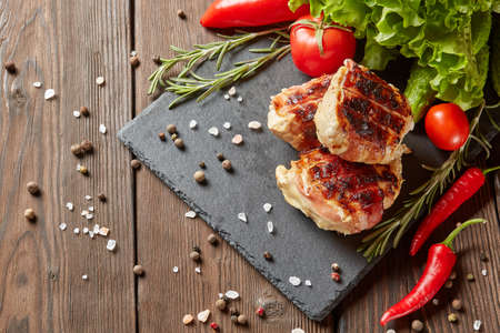 Bacon-wrapped grilled chicken (turkey)  fillet with fresh vegetables and spices on stone cutting board on wooden background. Top view with copy space
