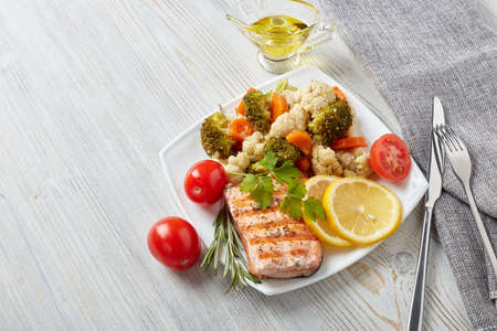 Grilled salmon fillet  garnished with vegetables, lemon, tomato, herbs lying on plate on wooden background. Top view with copy space.Healthy food. Keto diet.