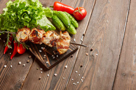 Shashlik from chicken with bacon. Grilled chicken (turkey) fillet on skewer and fresh vegetables with spices on stone cutting board on wooden background