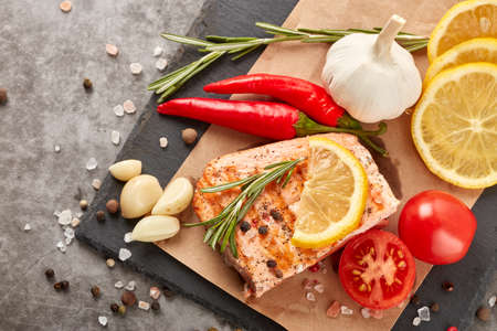 Grilled salmon fillet with spices and vegetables lying on stone cutting board on a grey background. Top view. Seafood menu.  Keto diet.