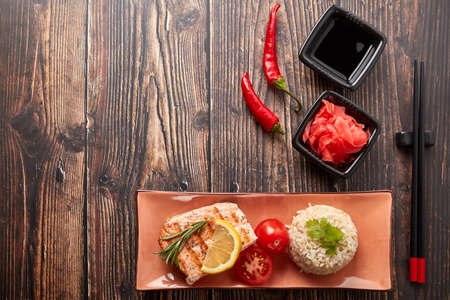 Grilled salmon fillet with rice, pickled ginger, soy sauce, tomato, lemon and herbs on dark wooden background. Top view with copy space. Healthy food.
