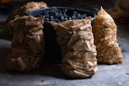 Bucket of carbon and sacks of pieces of wood photo