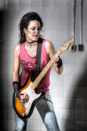Punk Girl playing guitar on an underground background photo