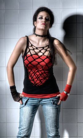 Punk Girl posing hard on an underground background photo