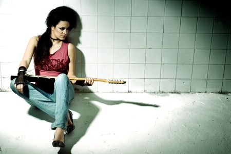 Punk Girl playing guitar on an underground background high contrast photo