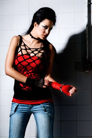 Punk Girl posing hard on an underground background high contrast photo