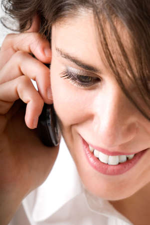 Young woman talking by telephone and smiling photo
