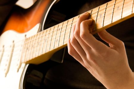 chord: Hand playing guitar chord with shallow depth of field and soft orange tone.