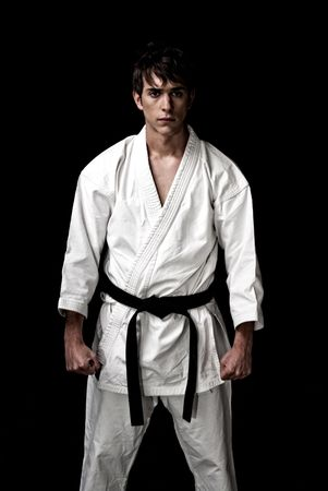 High Contrast karate male fighter on black background.  photo