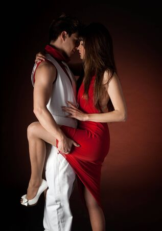 pareja bailando: Joven pareja de baile abrazo pasi�n rom�ntica sobre fondo rojo oscuro.